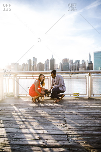 Vertical shot of a couple dressed up in formal clothes kneeling by their dog on a pier