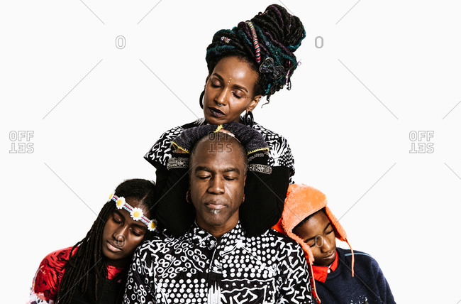 A medium shot of a spiritual black family in african clothing with eyes closed
