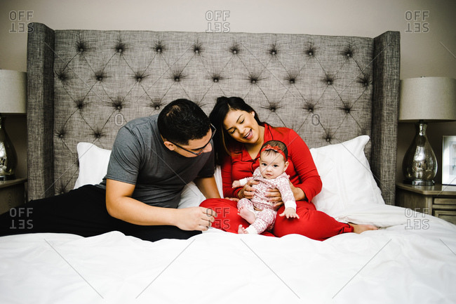 Horizontal portrait of a happy latino family playing with their daughter