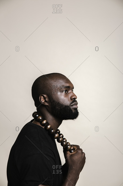 A side profile close up shot of a happy bald African American man with beard posing with a big beads necklace