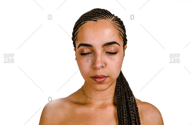 A young black woman sitting in front of a white wall with a long one sided ponytail