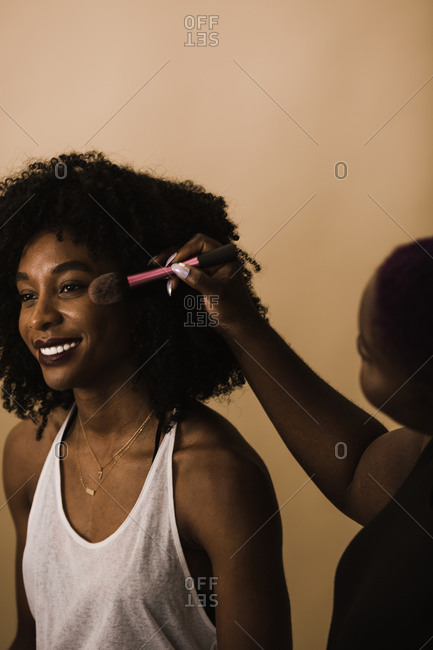 Vertical shot of a woman smiling while she gets her makeup done
