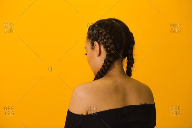 Back side of a Latina woman with French braids facing a gold wall