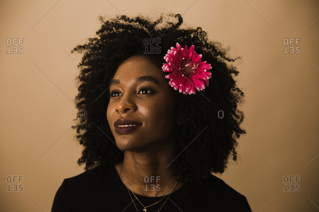 Guyanese woman posing with a pink flower in her curly hair