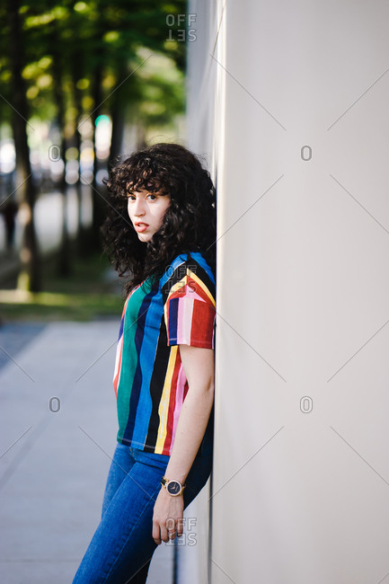 Latina woman wearing a colorful striped shirt posing outside of a building