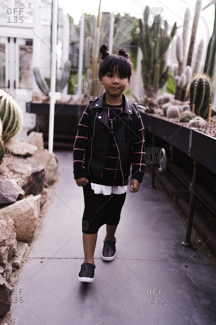 A portrait shot of a happy young Asian girl with pigtails walking in a botanical garden