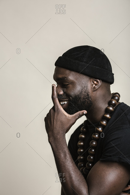 A side profile shot of a smiling African American man with beard wearing a black beanie cap posing with a big beads necklace