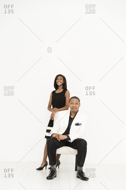 Vertical portrait of a black father sitting in a chair as his daughter leans behind on a white background
