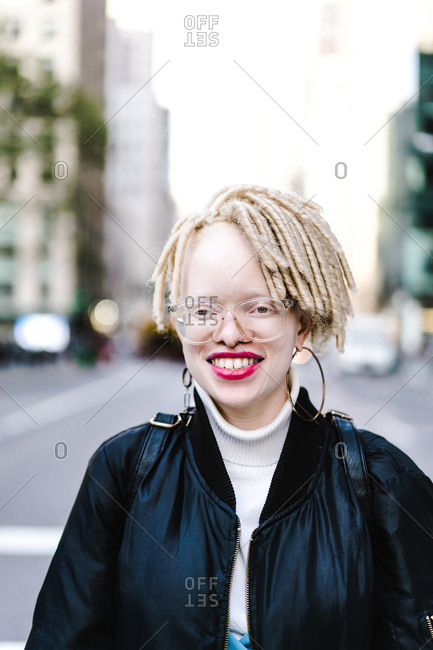 Vertical portrait of a woman wearing a jacket in the city smiles at the camera