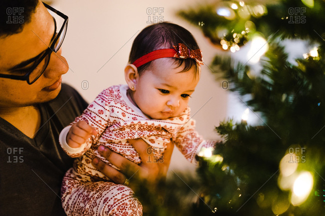 Horizontal shot of a latina baby being held by her dad gazing at the Christmas tree indoors