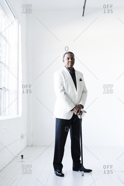 Vertical portrait of a man holding a fancy cane in a white suit looking at the camera