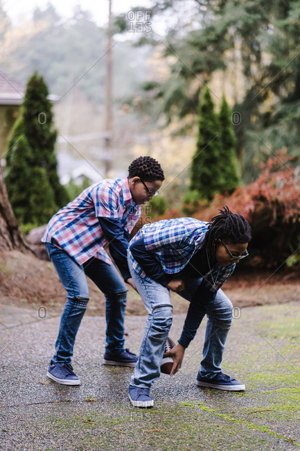 Young boy bending over and passing a football to his brother between his legs