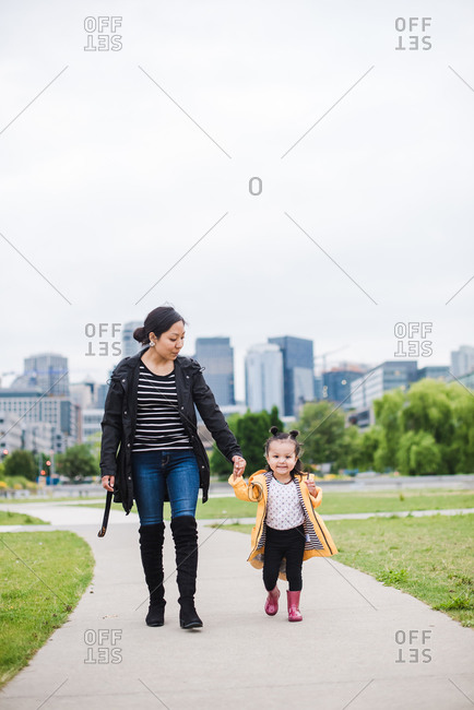 Happy mother and daughter walking on an empty track holding hands