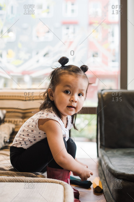 Side shot of a little girl sitting on a mattress and playing with wooden blocks