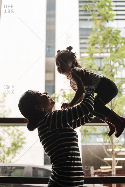 Vertical shot of a mother holding her daughter up in the air
