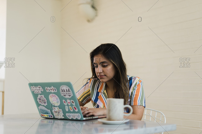 Wide shot of an Asian woman working on her laptop at her desk