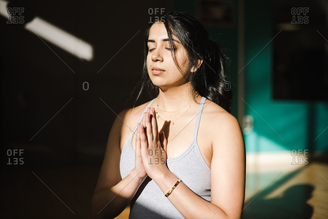 Graceful  young woman doing meditation in a studio