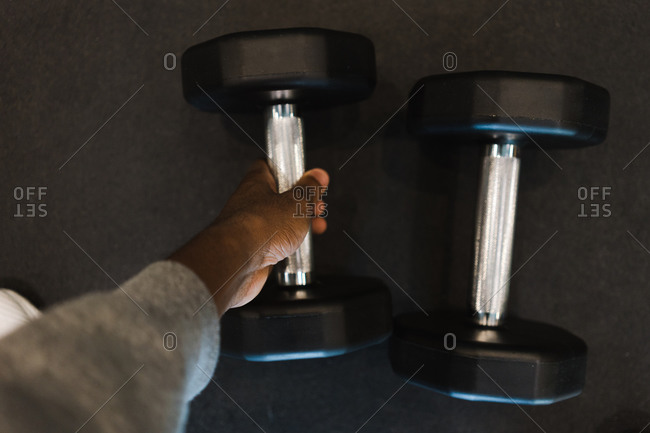 Close up of a man's hand lifting weight from a gray floor