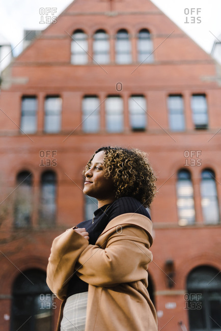 Vertical portrait of a young woman smiling and standing in front of a building