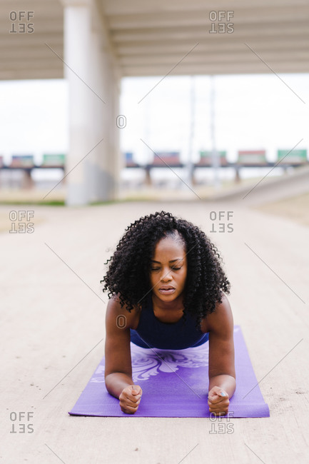 Strong focused woman performing yoga outdoors
