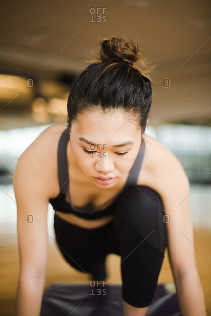 Vertical portrait of a young woman doing yoga on a mat in the gym