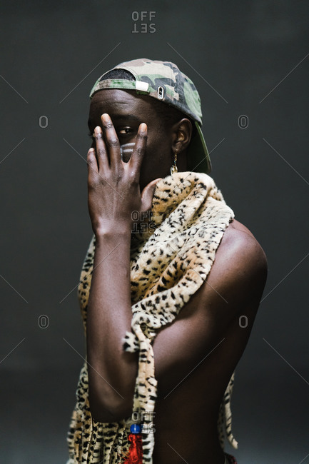 Young man in African attire covering his face with one hand and posing against a gray wall