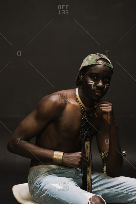 Young man in African attire sitting on a white chair and posing against a gray wall