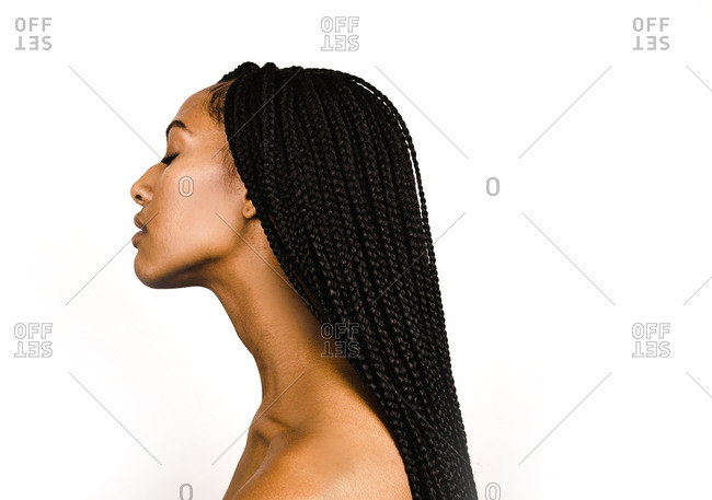 A side profile close up shot of a Black woman with long braids