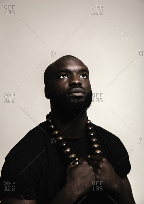 A close up shot of a bald African American man with beard posing with a big beads necklace while looking up