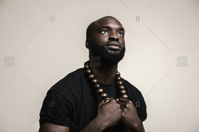 A portrait shot of a bald African American man with beard posing with a big beads necklace while looking up