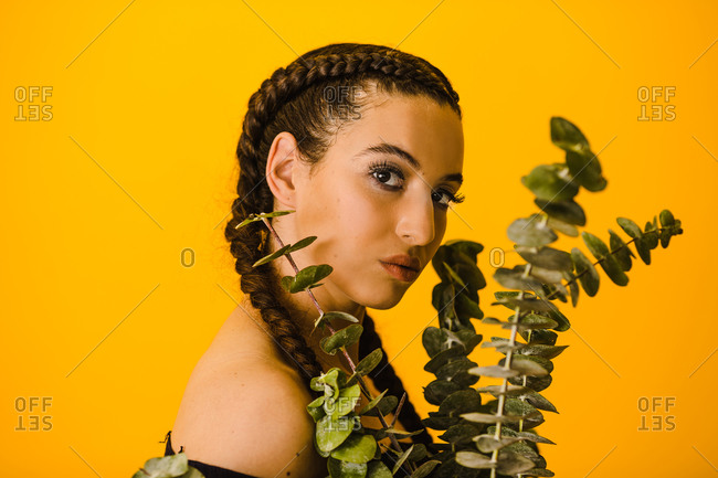 Portrait shot of a Latina woman posing behind a eucalyptus plant with a golden background