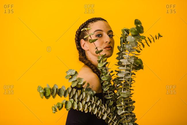 Latina woman posing behind a eucalyptus plant