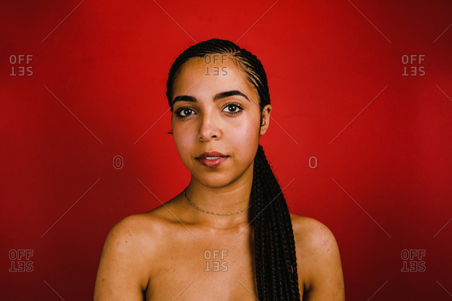 A young black woman sitting in front of a red wall with a one sided ponytail