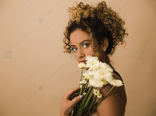 Side profile of a curly haired woman holding a bunch of flowers in front of a brown wall