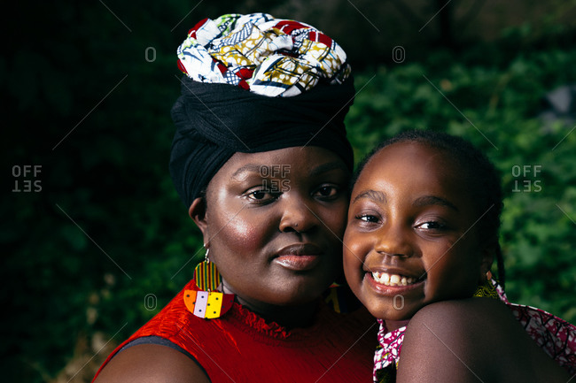 Young Black girl and her mother smiling at the camera on a sunny day in the park