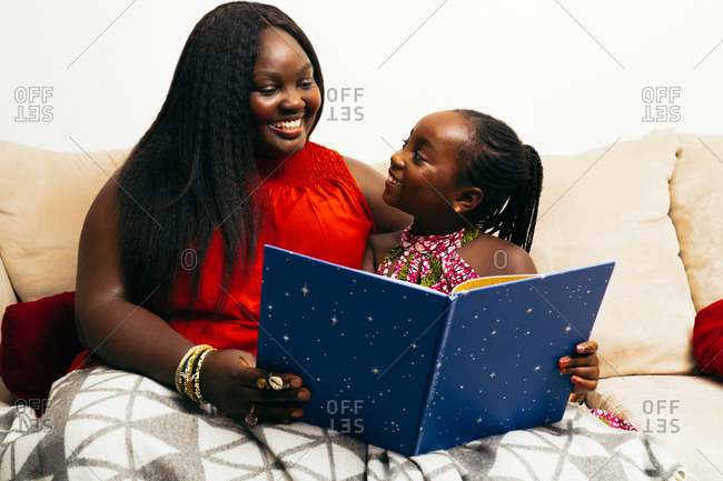Middle-aged black woman and her daughter looking at each other and smiling while reading a book on the couch