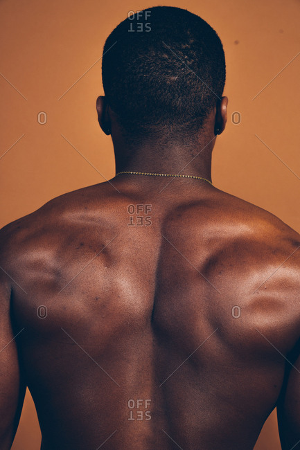 Rear view of a shirtless black man showing off his muscular back with an orange background