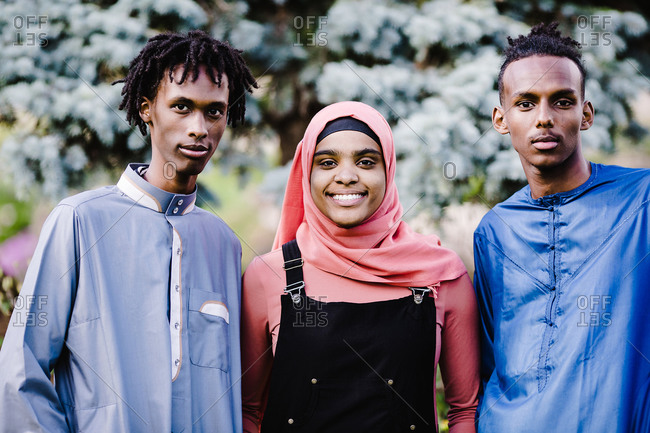 Young black Muslim men standing with a black Muslim woman in Islamic clothing
