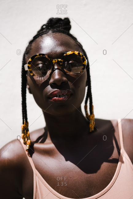 Vertical portrait of a woman with large sunglasses and braids wearing red lipstick