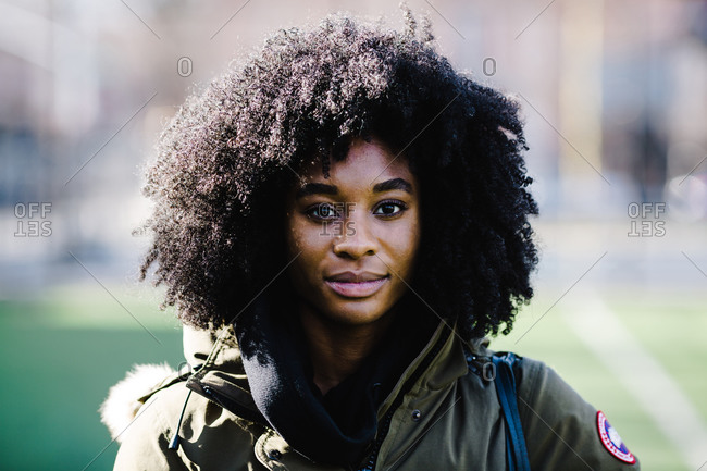 Close up portrait of a black athletic woman with curly hair standing on a grass field in a jacket