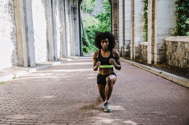 Black woman in athletic apparel exercising outdoors during daytime