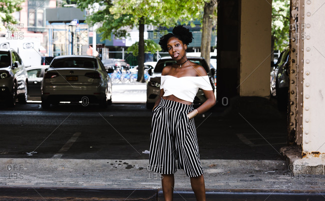 Medium shot of a fashionable black woman posing outdoors in an off shoulder crop top dress