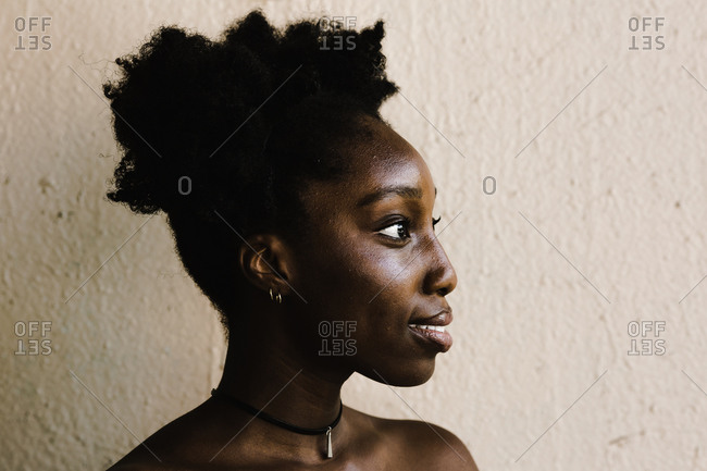 Side profile of a black woman with two afro puffs standing in front of a wall