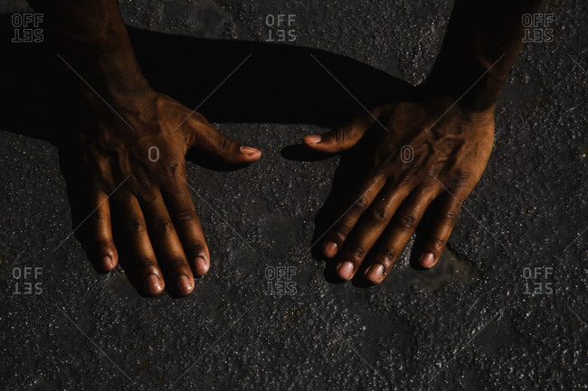 Close up of the hands of an athlete over a wet concrete ground