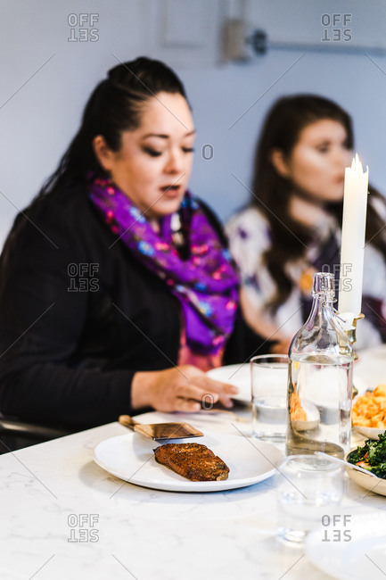 Vertical shot of a two ladies around the table having fun at a family dinner with selective focus