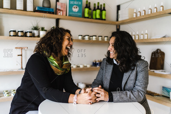 Horizontal waist up shot of lesbian couple sitting close holding hands at a restaurant table smiling at each other