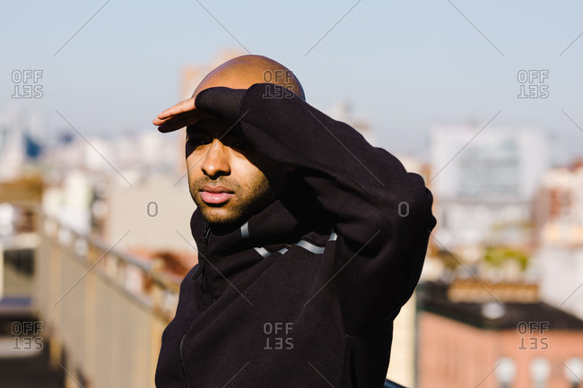 Bald man covers his eyes while working out outside