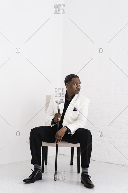 Vertical portrait of a man sitting in a white suit with a fancy cane looking sideways