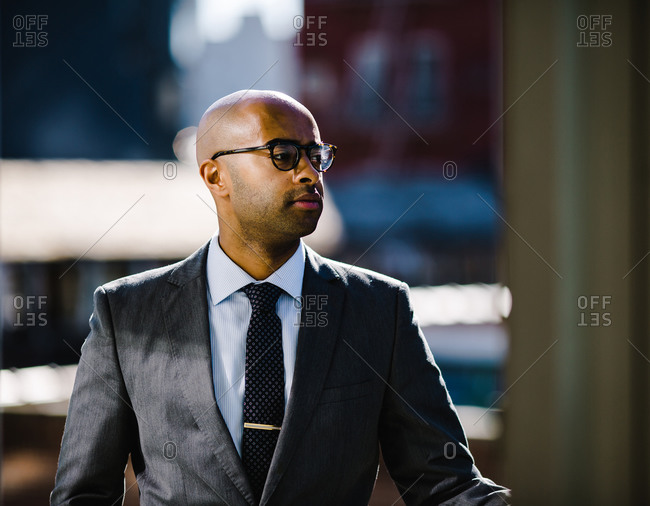 Professional man in a suit and glasses walking down a street