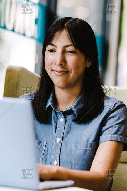 A close up portrait shot of a happy hispanic woman using a computer